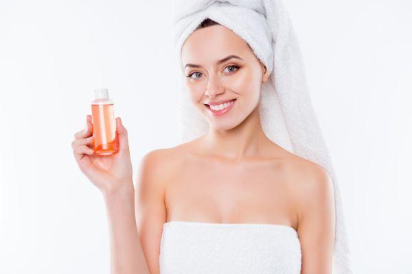ventajas-y-desventajas-de-los-champus-sin-sulfatos-mujer-toalla-en-la-cabeza-muestra-champu-istock
